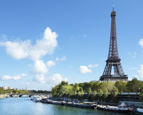 Eiffel Tower landscape taken from the south side, with River Seine, boats and blue sky with copyspace..